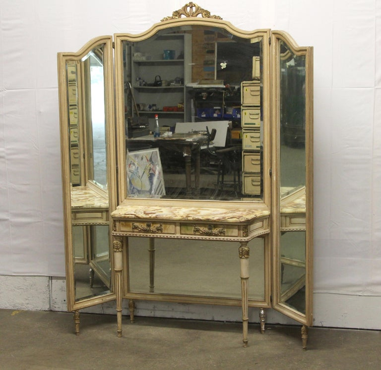 1920s French Provincial carved and hand painted wood vanity table with two drawers and an attached tri-fold mirror. It features a delicate onyx top table with orange, yellow and white veining. There is damage to the one leg. The dimensions are Table