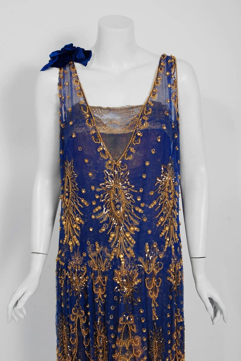 Undiminished by time, this 1920's royal-blue and gold dance dress still casts its seductive spell. This exceptional Art Deco beauty is fashioned in three different French couture fabrics- sheer silk chiffon, metallic gold lace and lamé based