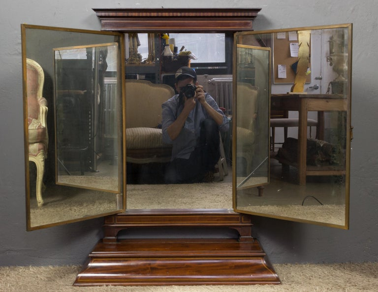 Triptych vanity mirror by Brot housed in a mahogany wood frame with storage box. A special detail of this piece is the boxwood inlays adorning the top and base of the wood frame.
