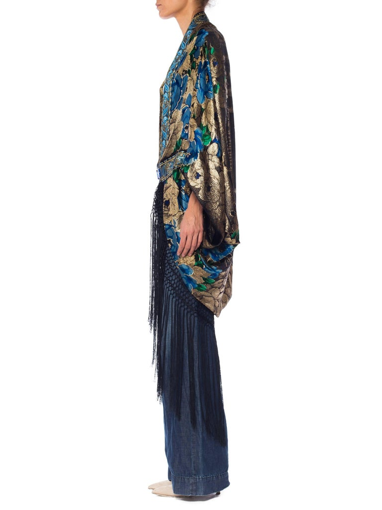 This magnificent cocoon is made from an antique silk and metal piano shawl from the 1920s. We trimmed it up with fine French ribbon with a complimentary paisley and metallic pattern in blues and greens. The fringe hem adds movement and romance and