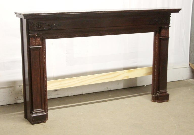 Large wooden Federal style mantel with a dark mahogany finish and decorative carvings. There is general wear from age and use. This can be seen at our 302 Bowery location in Manhattan.