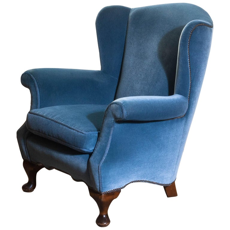 Unique and extremely beautiful Hollywood Regency club chair in blue velvet from the 1920s.