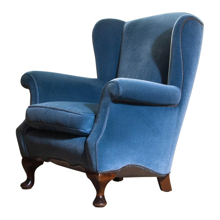 Unique and extremely beautiful Hollywood Regency club chair in blue velvet from the 1920s. The chair is completely restored in 1987 (only original materials are used). The overall condition of this chair is very comfortable and good