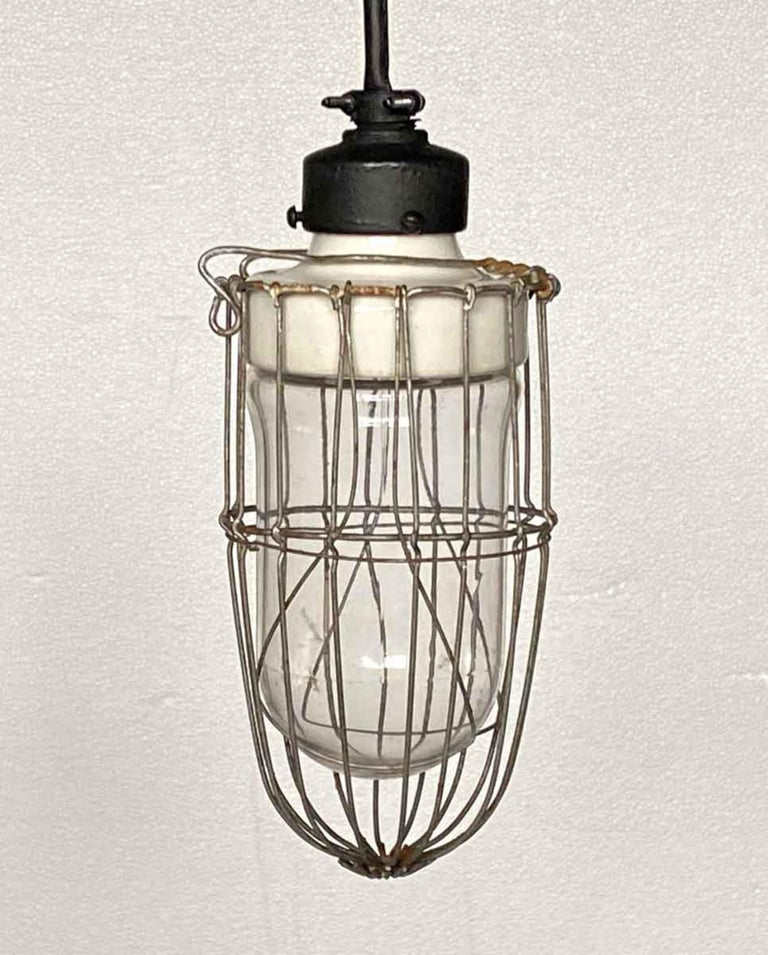 Industrial cage light with thick original porcelain fixture, circa 1920. This has been recently rewired with a long cord and matching black canopy. Please specify the overall drop that is needed upon purchasing. Small quantity available at time of