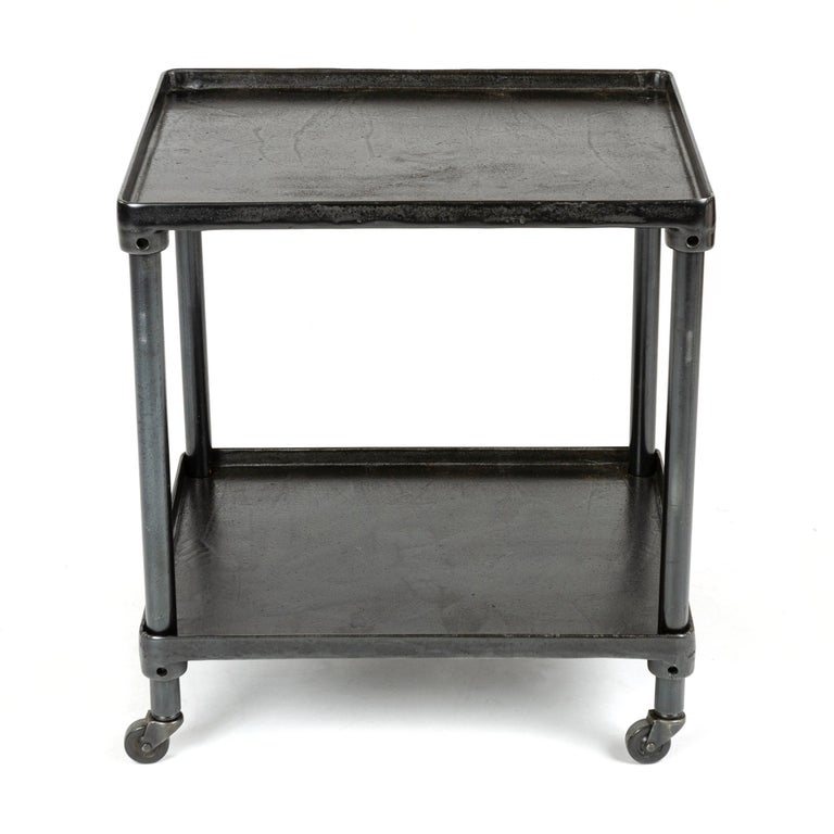 A patinated cast iron industrial cart on casters, with a 'tray' top and adjustable lower shelf.