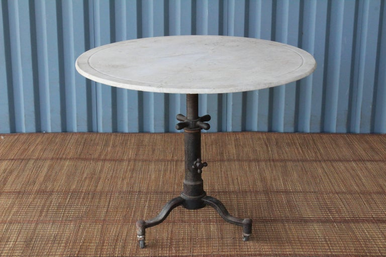 1920s Industrial cast iron table base on rolling casters with an antique marble top. This table is height adjustable and can be used anywhere between 25.5 inches high to 30 inches high. Marble top has age appropriate patina. Table base has slight