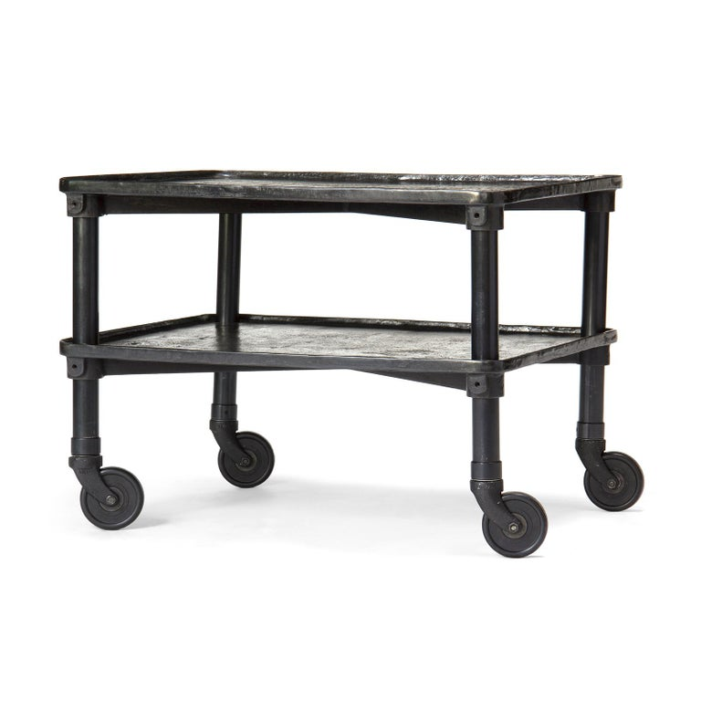 A patinated cast iron two-tier industrial table on single wheel casters.