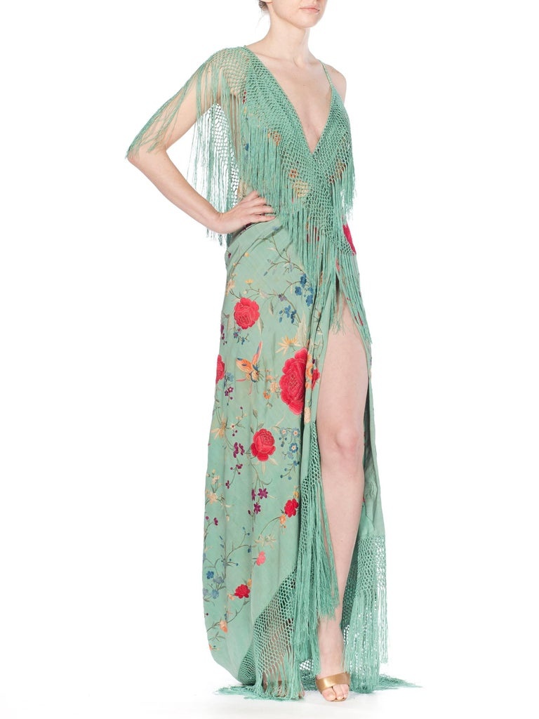 This gown is made from an antique piano shawl in the most beautiful Chinese Jade green with wonderful flowers and butterflies embroidered all by hand. The gown has a high slit and low back with a train. The train can be picked up and latched to a