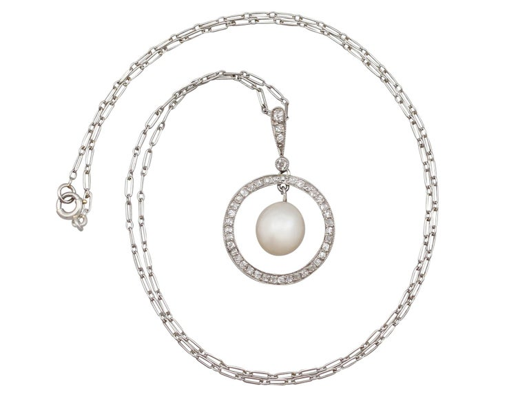 An impressive antique 1920's natural saltwater pearl and 0.44 carat diamond, platinum pendant and chain; part of our diverse antique jewelry collections.  This fine and impressive antique pearl and diamond pendant has been crafted in platinum.  The