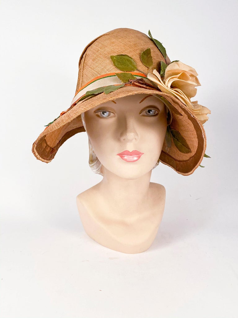 1920s hand woven natural colored panama day cloche with handmade silk flowers, three-toned (orange, green, and beige) grow-grain band, foliage, and pin pleat accents.