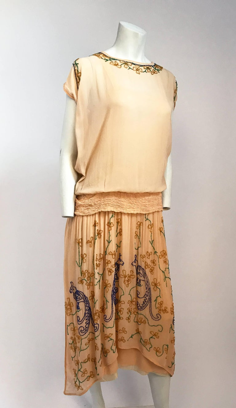 1920's Peach Glass Beaded Drop-waist Dress. Peach Drop-waist dress with multicolored glass beading featuring Peacock design. Smocked waist band that forms bow in the back. Built in lining and short dolman sleeves. Fits US Dress Size 5-6.