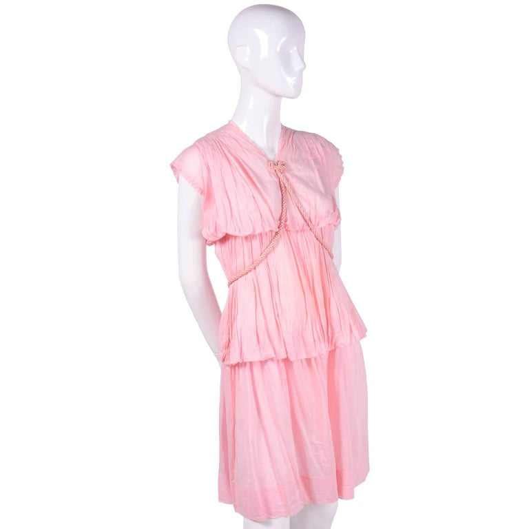 This is an absolutely beautiful vintage dress from the 1920's. The dress  is in a pink ultra fine cotton voile with tiers of slightly gathered fabric and an attached braided pink satin rope belt. The belt can be worn Grecian style or worn a number