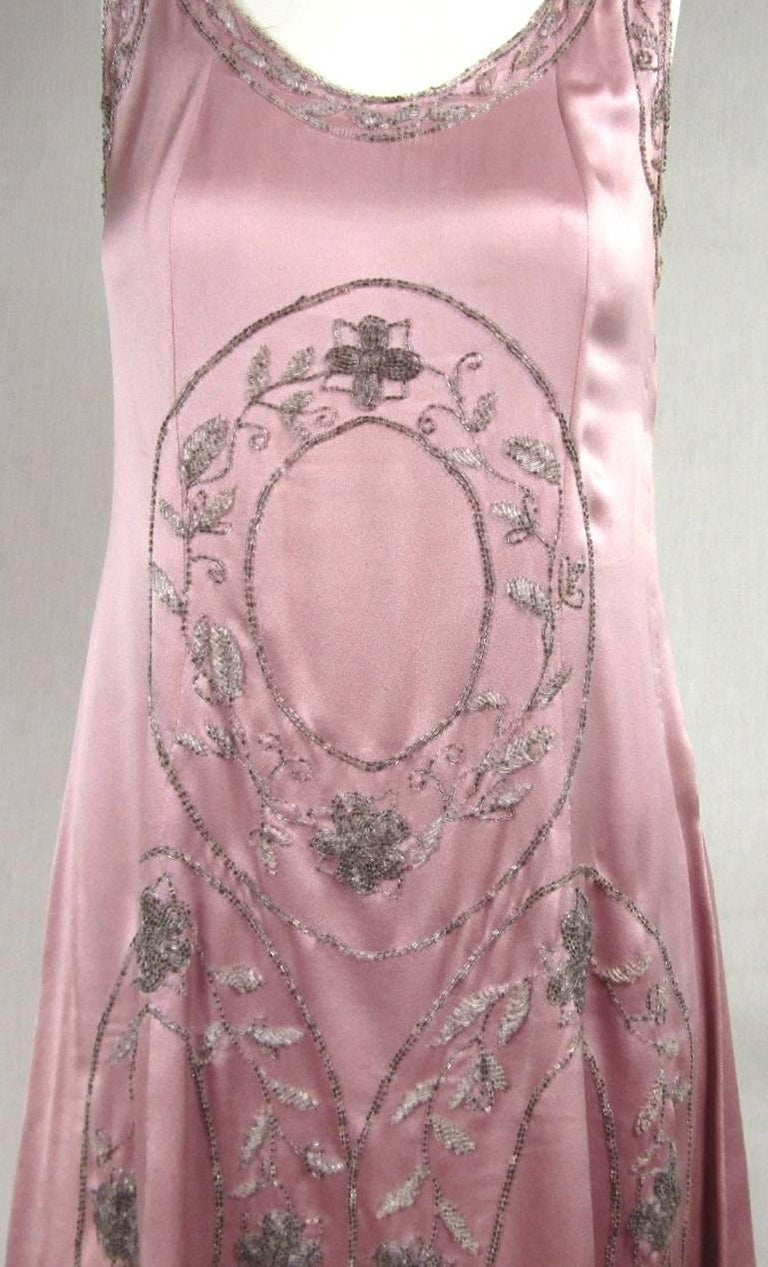 They are getting harder to find, and even harder to find in wearable condition. This silk pink dream is all hand beaded. Stunning T back. Bugle beading around the neckline and arms. Snaps up the left side, no slip needed. Will fit a medium. It was