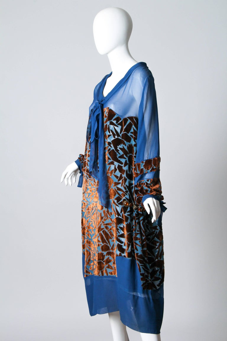 This is a lovely blue silk afternoon dress from the mid-1920s. The sheer base fabric is embellished from the bust to the knees and around the lower arms with beautiful chestnut-brown voided velvet. The velvet is cut in an abstract geometric pattern