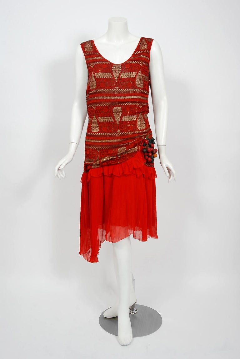 Breathtaking 1920's flapper dance dress in the prettiest metallic gold and red color combination. The garment's simple unstructured style is so modern; the fine couture fabrics are a treasure trove of needle art. The dress is fashioned from