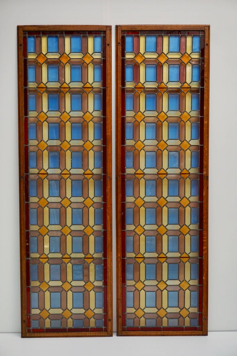 Two stained and multicolored leaded glass window panels in wood frame (Priced each). Measures: Height 194 cm. Width 58 cm. Weight 10 kg.  Price per item.