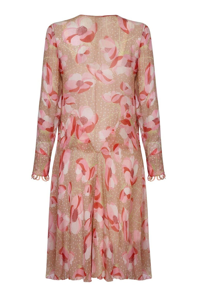 This charming 1920s silk chiffon floral print dress is delicate, feminine and in beautiful vintage condition. The sheer chiffon fabric hosts a bold poppy design in soft pink shades over a warm fawn backdrop and has an air of understated modernity.