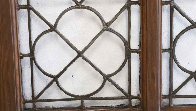 Oak door with quatrefoil leaded glass design from a turn of the century upper east side Manhattan estate. They are a dark wood tone on one side and are painted black on the opposite side. There are minor cracks in the glass. Two Available, priced