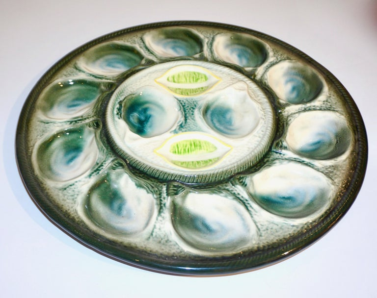1920s French Art Deco Majolica set of 6 oyster dishes complete with a serving platter for 12 oysters and lemon halves. A set signed by St. Clement Frères, a factory with a very old tradition in