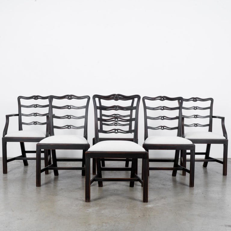 This set of six wooden chairs was made in the United Kingdom, circa 1920. The pure white upholstered seats complement the rich and warm umber shade of the wood. Carved top rails and ridges on the wooden frames show the meticulous craftsmanship