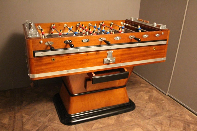 This foosball table is very unusual because it features a honey color wood. It still has got its four original ashtrays, as well as all its polished aluminum pieces. Its players are red and blue and its playground is black. Its shape is very elegant