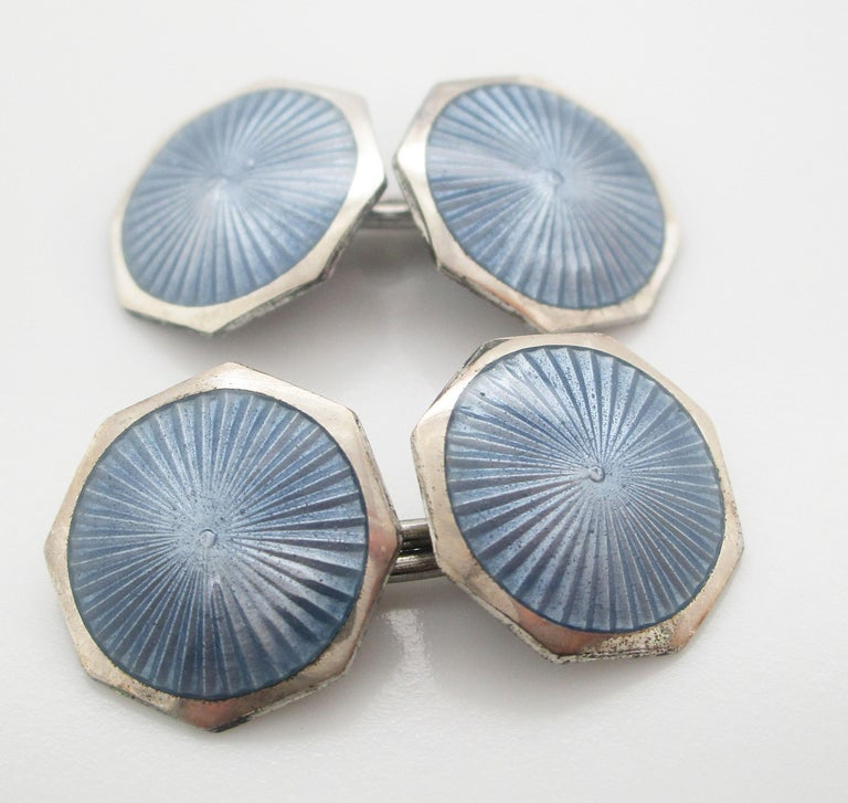 These cufflinks deliver the classic elegance of the Art Deco era in an elegant combination of sterling silver and steel blue enamel. The links have a sleek octagonal shape with a sterling silver border and a subtly detailed radial guilloche enamel