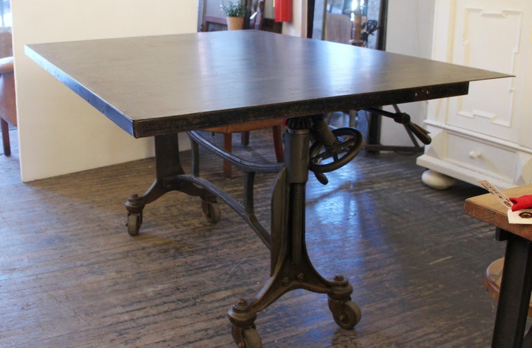 1925 Hamilton printer's table with a black finished wheeled cast iron base and steel top. Table top has two positions, flat for day to day use and vertical for storage. Height is adjustable. There are some scratches and surface wear from age and
