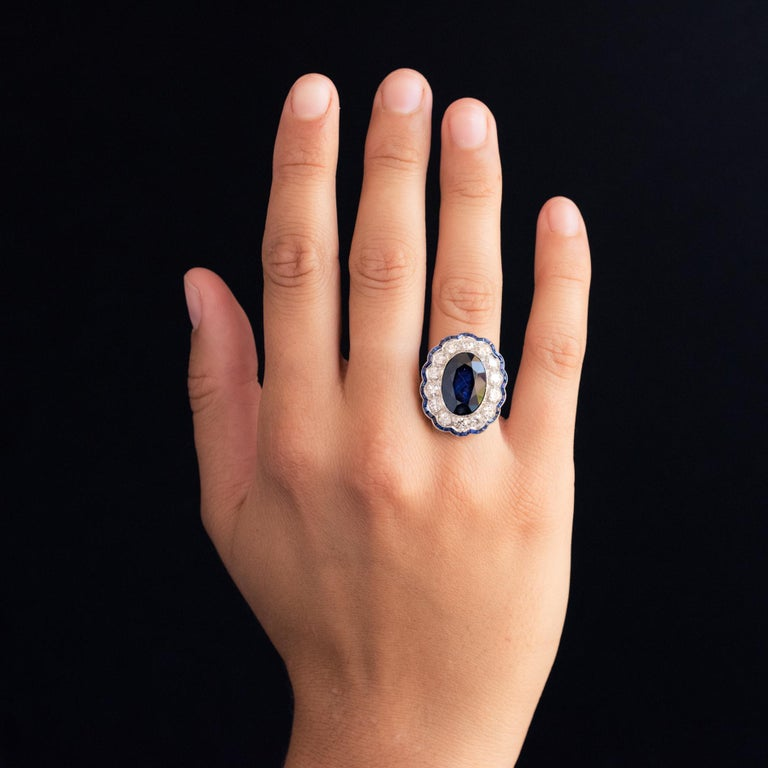 Ring in platinum. Oval in shape, this magnificent Art Deco ring is adorned on its top with a blue sapphire supported in a millegrain setting, surrounded by antique brilliant-cut diamonds, bordered by calibrated blue sapphires on a multi-lobed