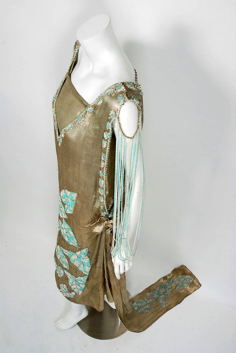 Breathtaking 1920's French couture museum-quality beaded & jeweled metallic lamé evening trained dress. The dramatic gold color palette touches a deep chord in our collective aesthetic consciousness. As fashion lovers, we never tire from antique