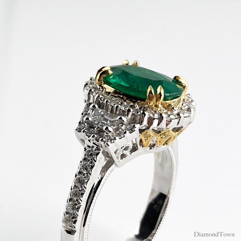 This gorgeous ring features a 1.93 carat Oval Cut emerald center, surrounded by a halo of round white diamonds.  With two tapered baguettes and additional round diamonds along the side shank, the total diamond weight is 0.68 carats.  Yellow gold