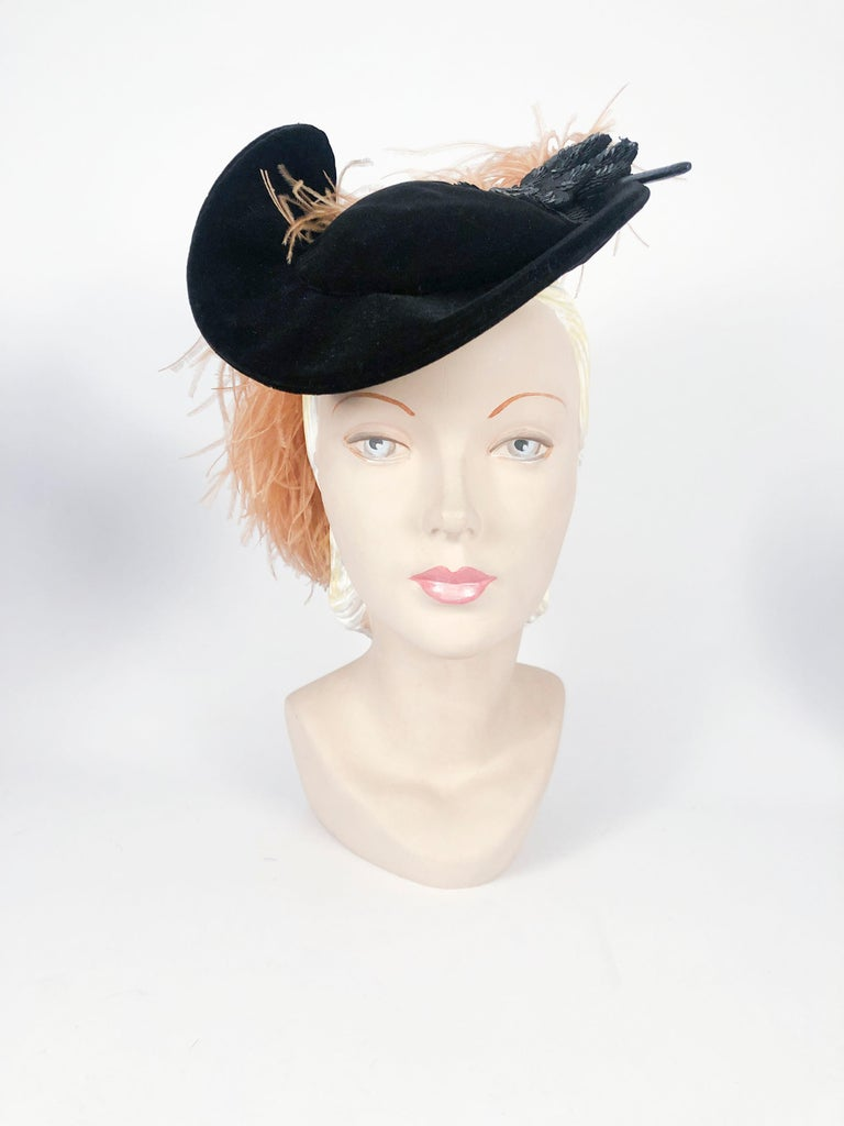 Late 1930s/ Early 1940s black velvet fashion hat with black sequin clover-shaped appliqué finishing a apricot-colored plume of marabou feathers.
