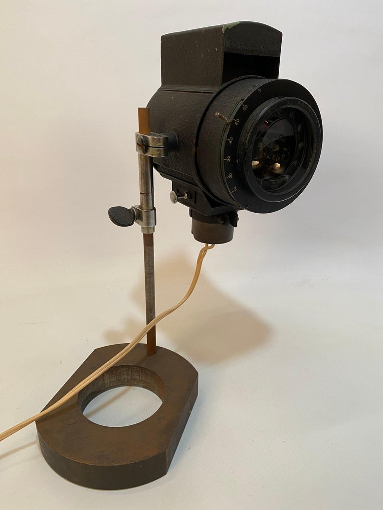 Adjustable table top spot light. Black powder coated. Height and angle can be hand adjusted. Hand adjusted aperture. High powered concentrated light. Older working wiring that is isn very good condition. No visible scratches to the lens.  Possibly
