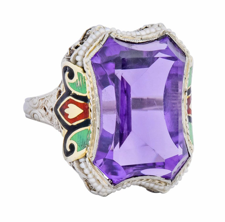 Centering a medium-dark purple amethyst fancy cut into an hour glass shape  Bezel set and surrounded by strung seed pearls, very well matched and white in body color  Flanked by yellow gold foliate motif glossed with black, green, and red enamel