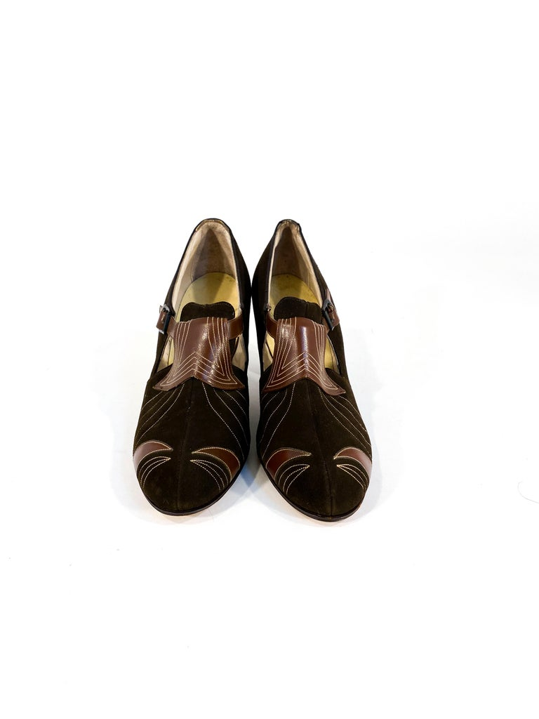 1930s brown suede and leather heels with Art Deco top stitching, cut outs, and metal buckle. The heel measures 2.5 inches from the ground.
