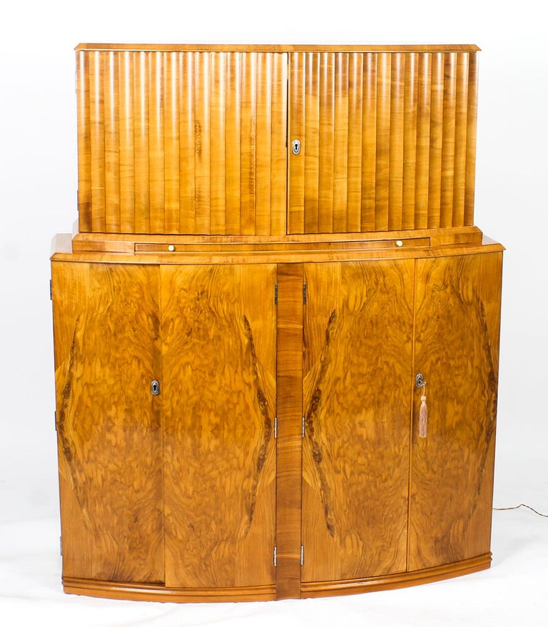 This is a fantastic antique Art Deco burr walnut bow fronted cocktail cabinet, circa 1930 in date and in the manner of Epstein.  This beautiful cabinet's upper part comprises a pair of ripple panelled doors enclosing a striking fitted mirrored