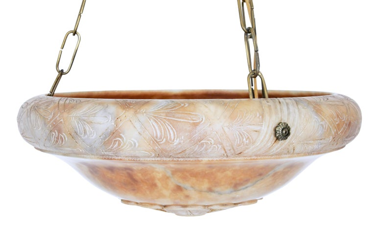 Beautiful carved alabaster chandelier, circa 1930.  Circular alabaster bowl with intricately carved edge and carved flower to the base of the bowl. Supported by 3 brass chains which lead up to a matching alabaster ceiling rose.  Fitted with 3