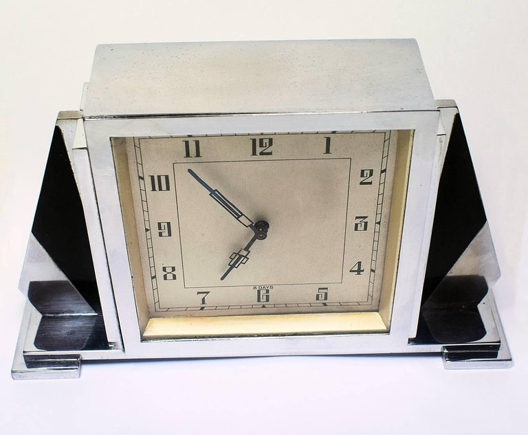 For your consideration is this rather stylish English Art Deco chrome clock with an 8 day movement. Deceptively heavy and of a good quality build. On the back of the clock reads 'British Made'. The black and chrome side fins make this a very