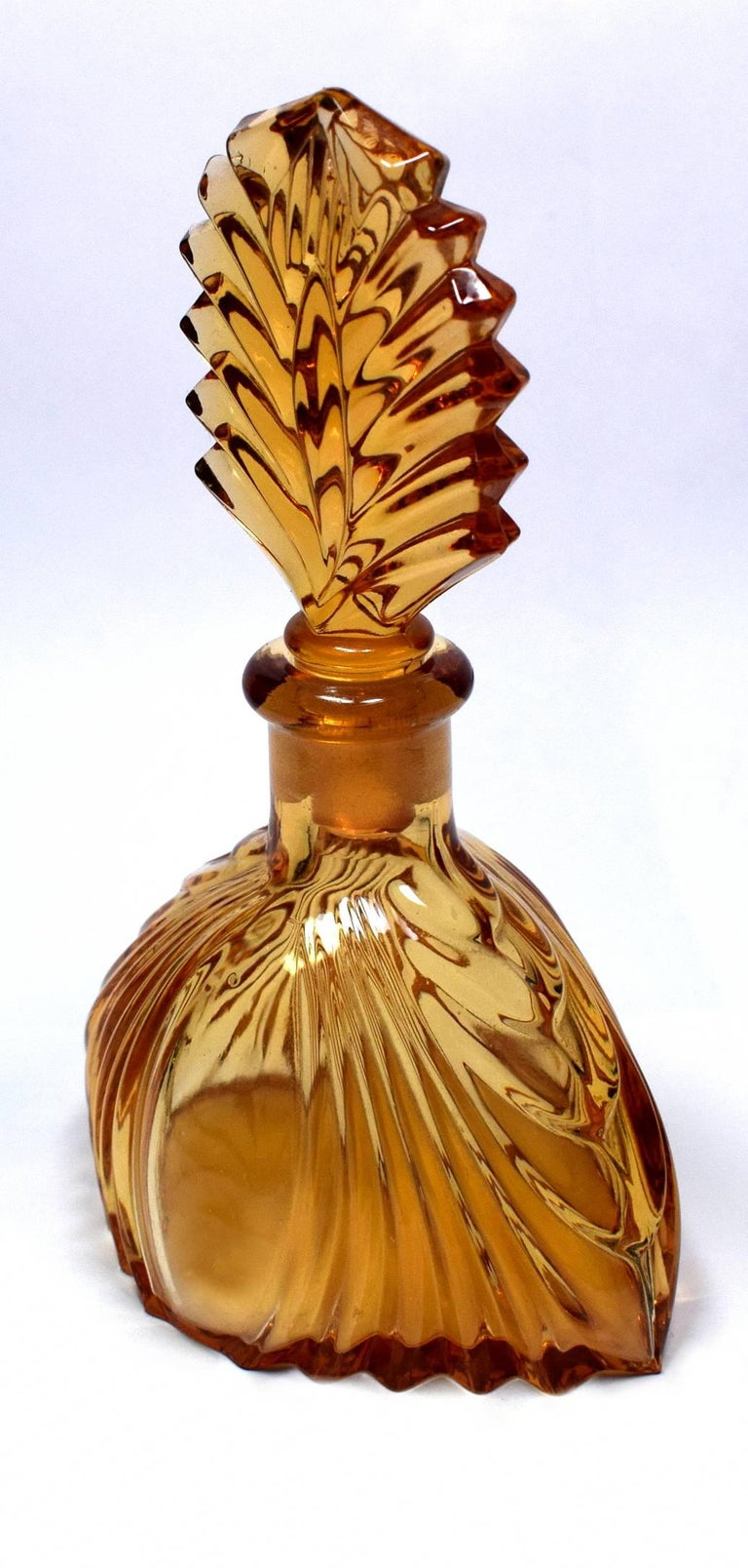 A really beautiful amber and clear colored Art Deco perfume bottle with a wonderful fan shaped glass stopper. In excellent condition with no chips or signs of use at all. A real collectors item for your Art Deco setting.