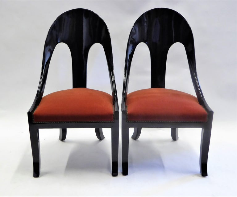 Period 1930s spoonback chairs with saber legs and a klismos bend, this pair of chairs are an elegant statement. Richly lacquered and with a deep burnt red Mohair velvet and nailhead upholstery, restored.
