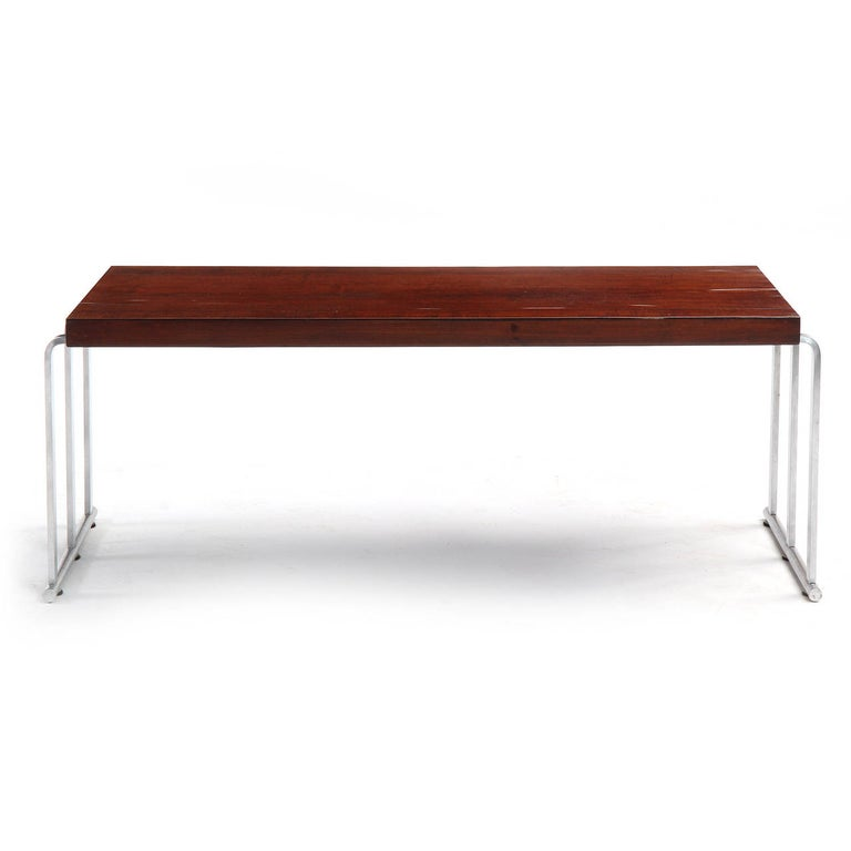 A low table or bench with a rectangular mahogany top floating a bent chromed steel base with sled feet.