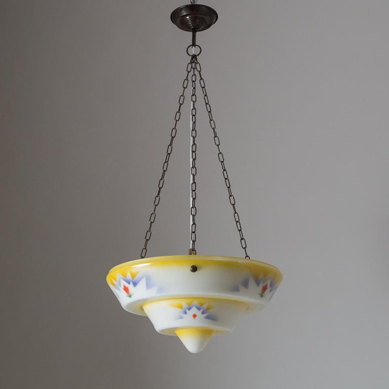 Rare Art Deco enameled glass pendant, circa 1930. A large tiered and cased glass diffuser is enameled in an unusually colorful design and suspended by patinated brass hardware. Good original condition with some small chips along the rim of the glass