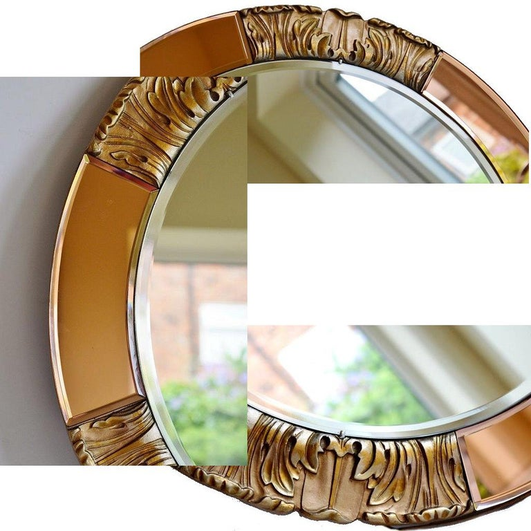 Mounted on the original stippled and gilded wood backing, this lovely Art Deco mirror has the original makers label for