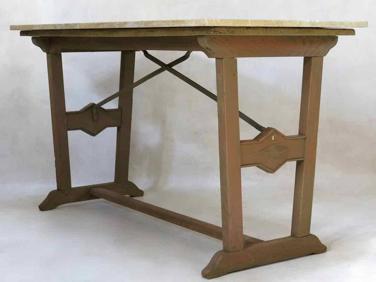 Unusual bistrot style table with an oak and iron base, topped with a thick slab of yellow marble. The uprights taper in towards the base and are decorated with a diamond-shaped design. Original, distressed brown paint on the wood.