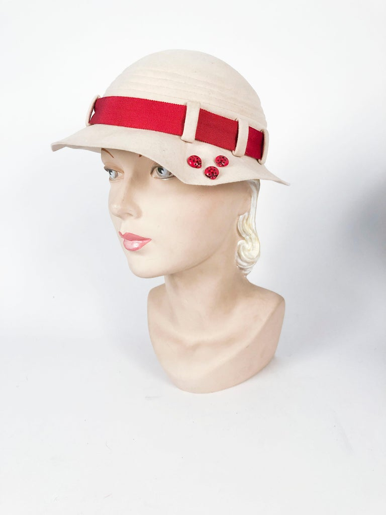 Sculpted 1930s beige fur felt hat with rust-colored grosgrain band finished with an art deco button. The sculpted brim has 3 ladybug accents that add an asymmetrically to the hat.