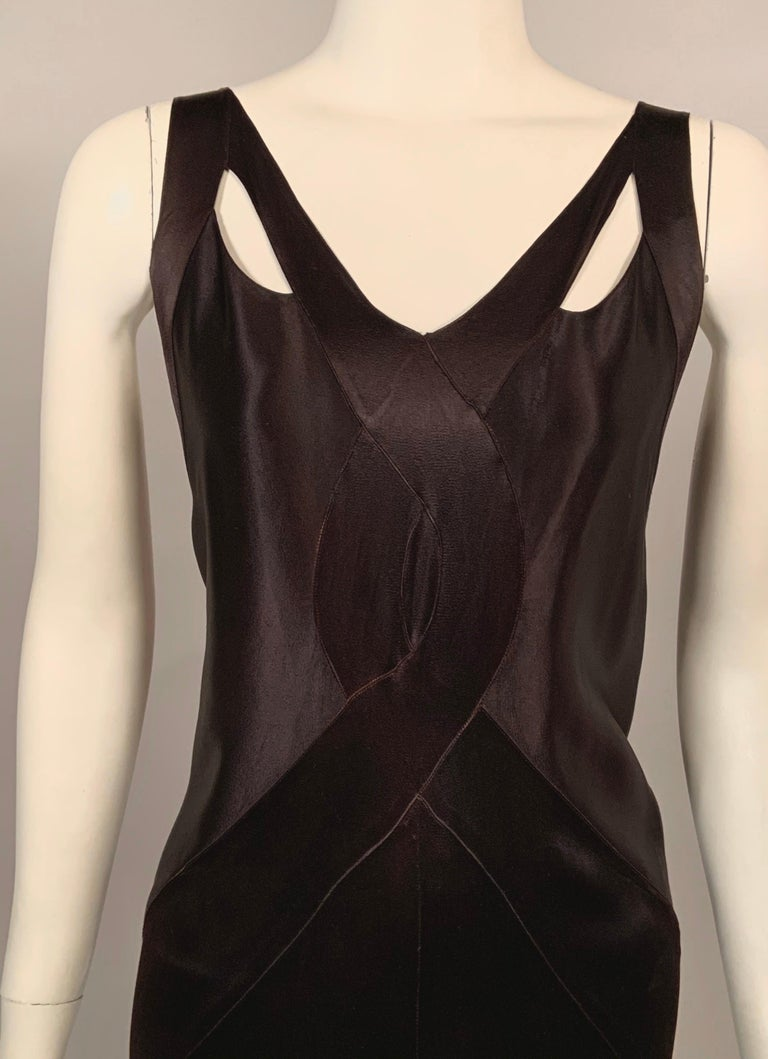 This very sexy black bias cut satin dress is trimmed with wide bands of the same satin edging the neckline and criss crossing at the center front. The bands widen and wrap over the hips to terminate at the center back ruffle and drape. The arm holes
