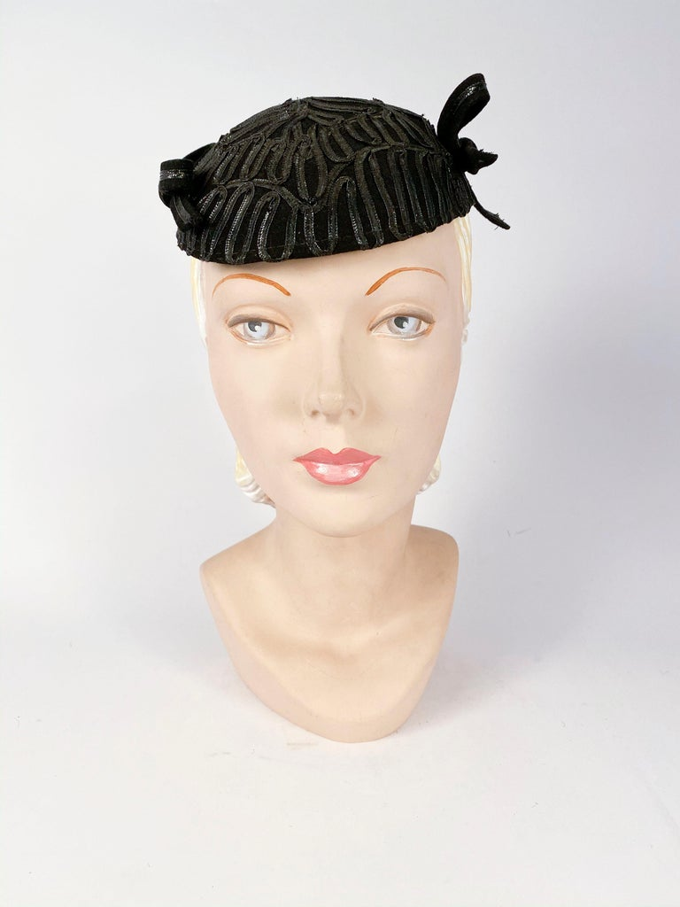 1930s black fur felt hat with black raffia accents along the entire body of the hat and finished with two raffia/felt bows on the sides.