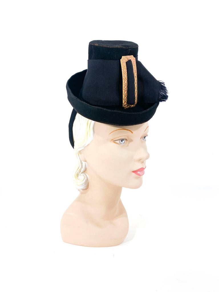 Late 1930s black fur felt toy pilgrim hat with a wide grosgrain ribbon band and large decorative brass buckle. The structured security ring is covered in matching black fur felt and fixes the hat to the head.