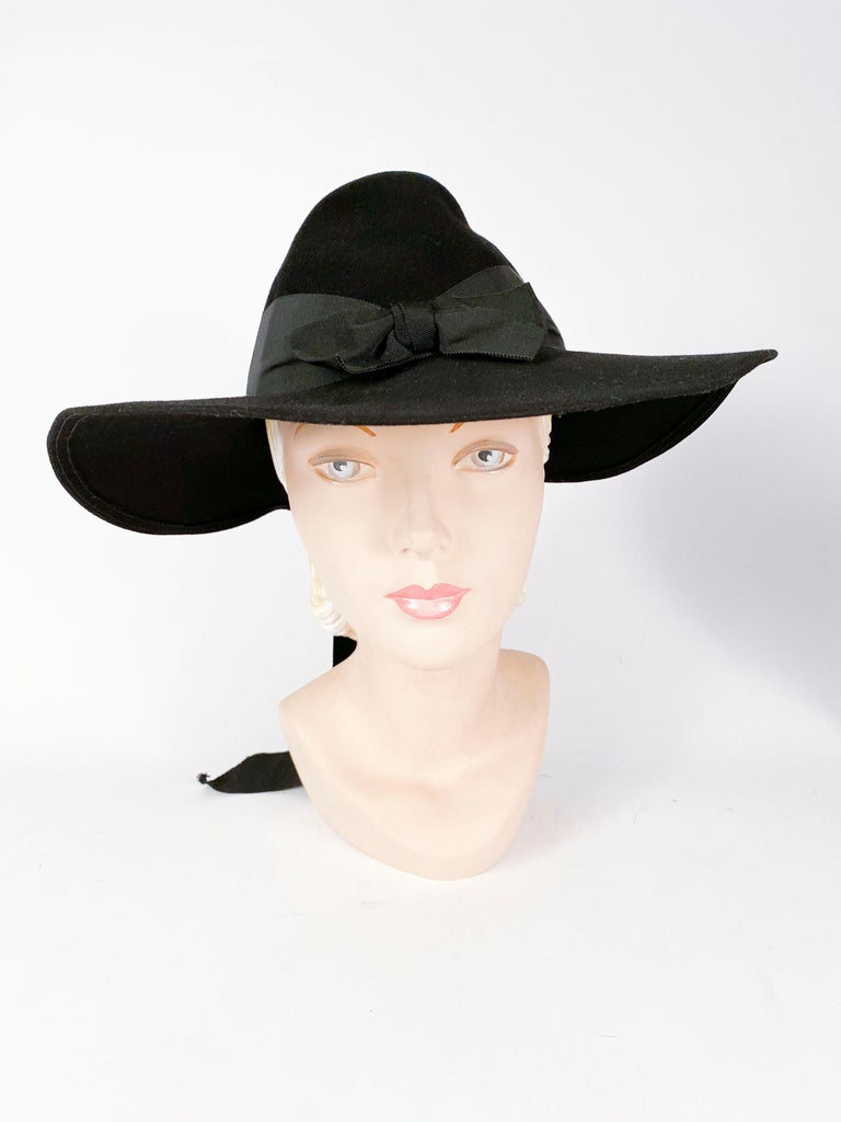 1930s black beaver fur felt wide-brimmed day hat with large bow centered in the front and the back of the hat. Finished with matching wide grow-grain tails.