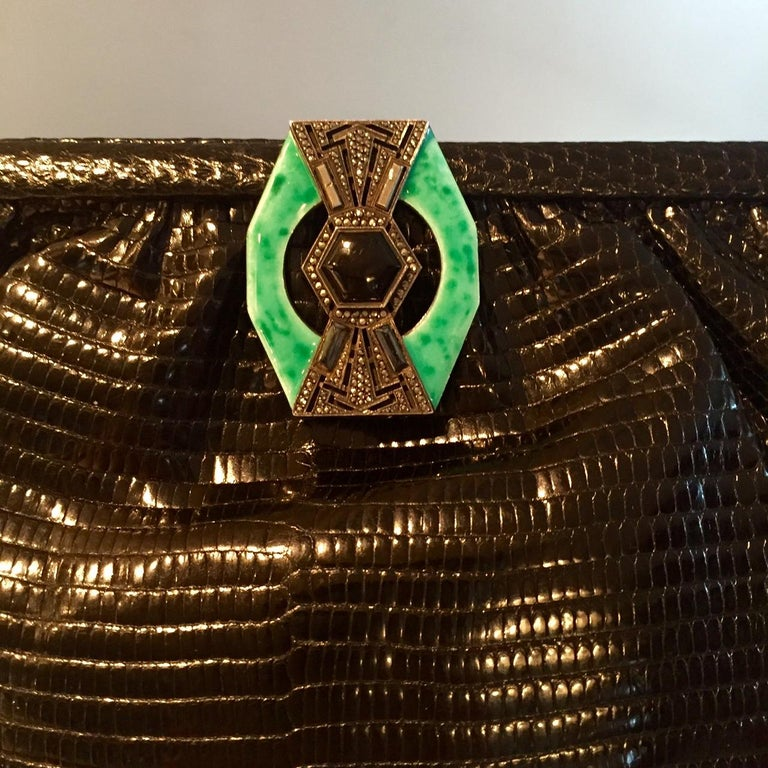 This Art Deco black lizard bag adds a touch of vintage glamour to any outfit. There is an unmarked silver clasp [which I believe is sterling silver ] decorated with marcasites, an onyx stone in the center and bands of chrysoprase on either side.