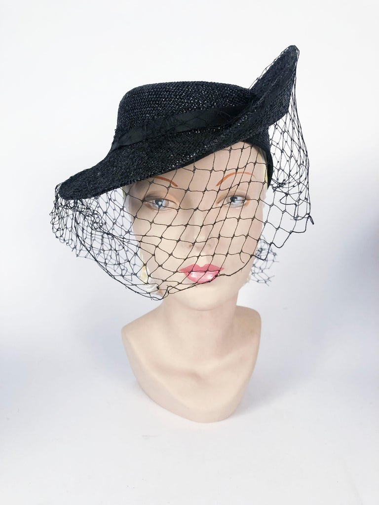 1930s black woven straw hat with asymmetrical brim, gros-grain band, and a full matching net. There is an elastic hair band that further holds the hat to the head.